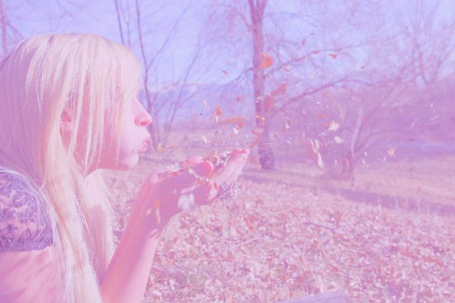 girl blowing leaves purple hue